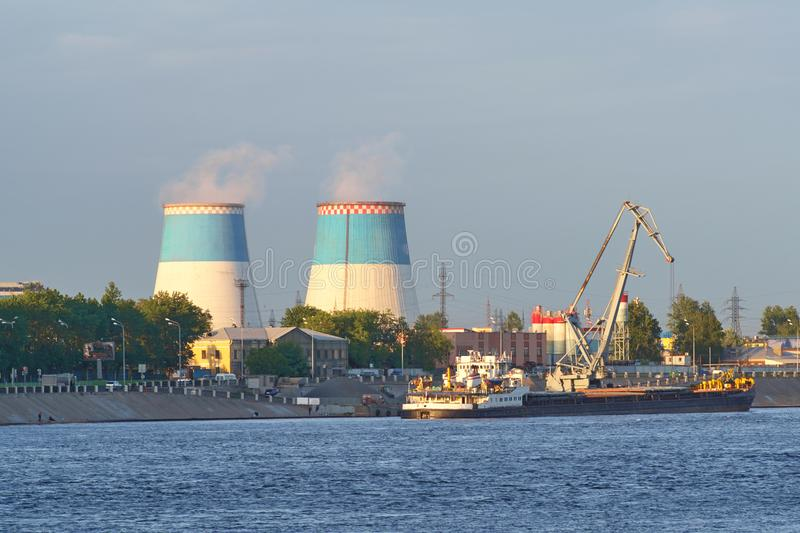 The towers of a thermal power plant, against a background of the. A thermal power plant produces electricity, a source of thermal energy in centralized systems stock images