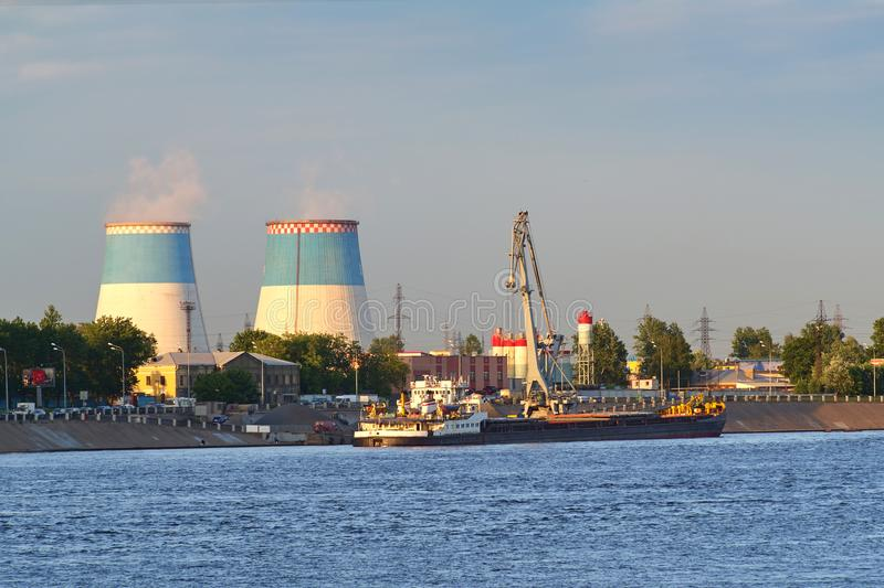 Towers of a thermal power plant, smoke against a blue sky background. A thermal power plant produces electricity, a source of thermal energy in centralized stock image