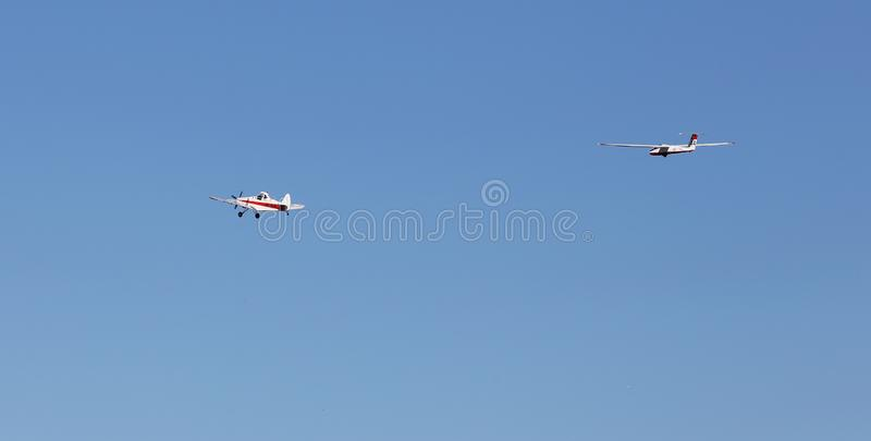 Towing glider. Gnesta, Sweden - September 20, 2015: An aircraft Piper PA-25-235 Pawnee towing a sailplane Pilatus B4-PC 11 against a clear blue sky royalty free stock images
