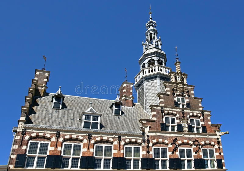 Town Hall, a world heritage site in city Franeker. Netherlands: The frontage, with tower, of the medieval city hall. In the facade is the city coat of arms, with royalty free stock photo