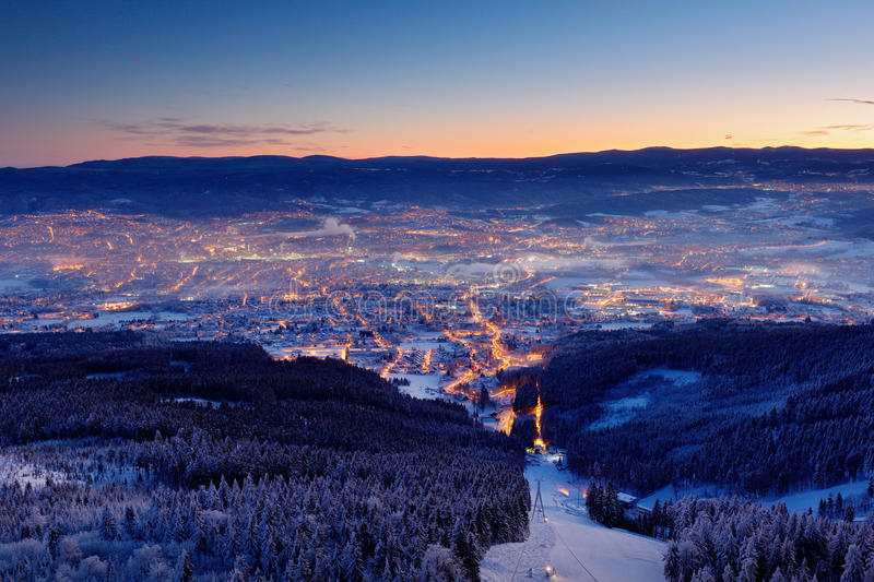 Town Liberec with winter mountain forest before sunrise. Czech early morning snow landscape pink and violet light. Snowy trees wit stock images