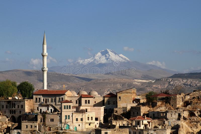 The town of Ortahisar in Cappadocia with Mount Erciyes in the background royalty free stock image