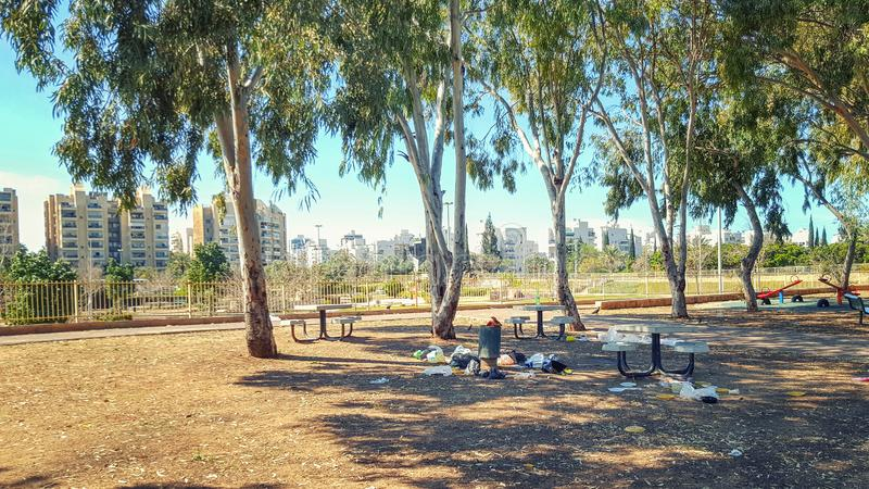 Town park and recreation facilities are littered. A small town park provides neighborhood dwellers with picnic facilities in form of solid concrete tables and stock images