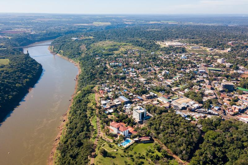 Town of Puerto Iguazu city centre aerial view. Fraternity Bridge border crossing Brazil-Argentina over the Iguassu River. Town of Puerto Iguazú city centre stock photo