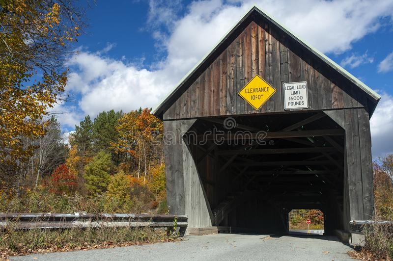 Fall foliage surrounds the Linclon Covered Bridge over the Ottauquechee River in West Woodstock Vermont. royalty free stock images