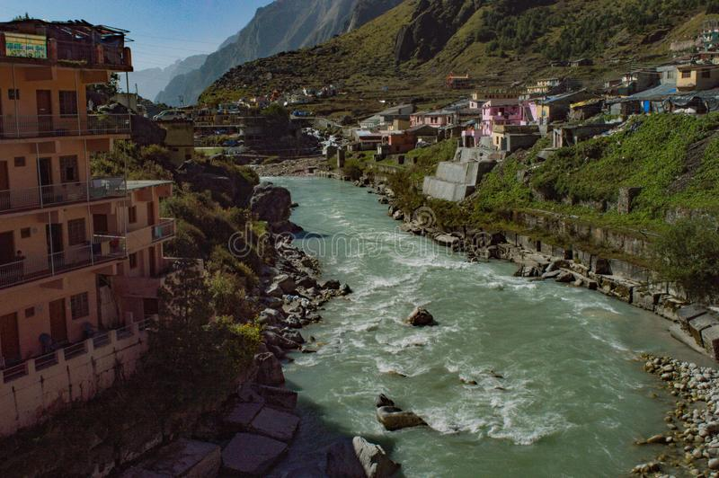 Town on river side. House, city, hill, water, sky, emerald, alakananda royalty free stock image