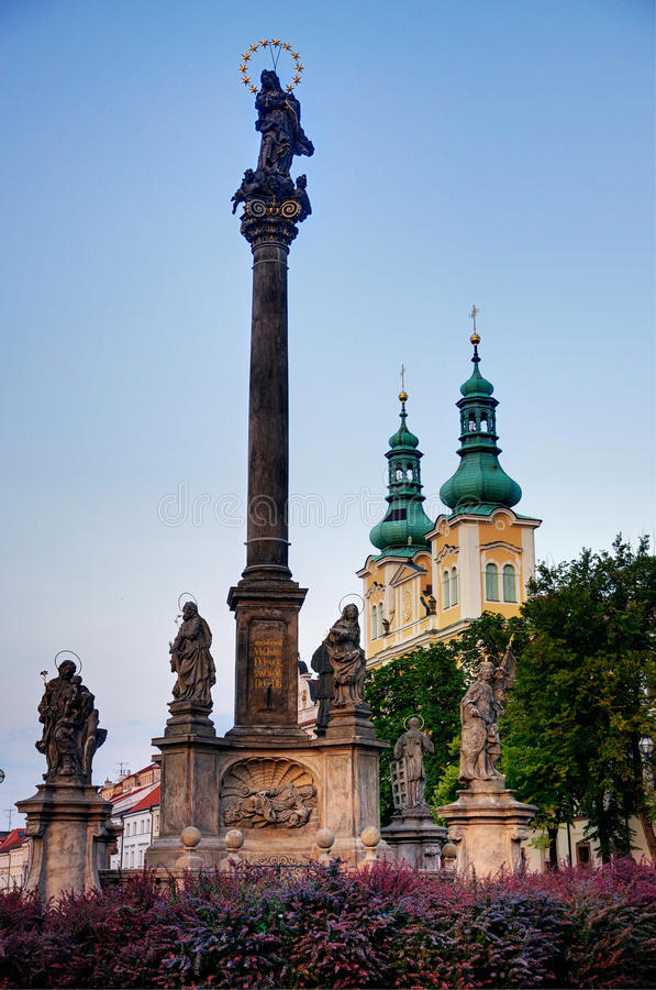 Town Square of Hradec Kralove. In the evening. In the foreground the plague monument can be seen. The church in the back is the Church of Assumption stock photography