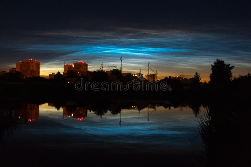 Town view of noctilucent clouds NLC. Beautiful waves and ripples of silver blue night shining clouds over some houses in summer. Town view of  noctilucent clouds royalty free stock photos