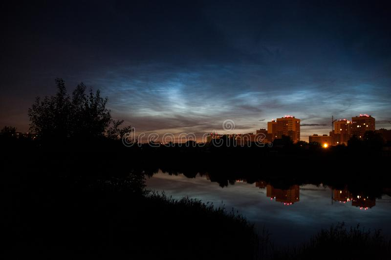 Town view of noctilucent clouds NLC. Beautiful waves and ripples of silver blue night shining clouds over some houses and trees. Town view of noctilucent stock image