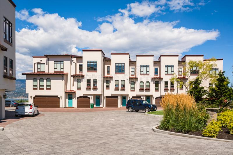 Townhomes with wide garage door and cars parked in front. Residential townhouses with scenery view on a lake and mountains. Townhomes with wide garage door and royalty free stock photo