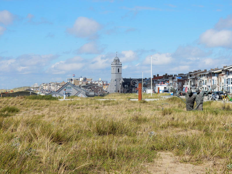 Townscape Katwijk aan Zee med kyrkan, boningar och dyn med gräs arkivfoto