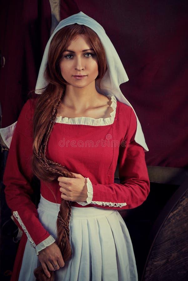 Townswoman στο κόκκινο φόρεμα με μια ποδιά και chaperone στην οδό στοκ φωτογραφία