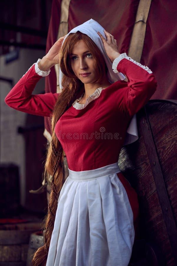 Townswoman στο κόκκινο φόρεμα με μια ποδιά και chaperone στην οδό στοκ εικόνες