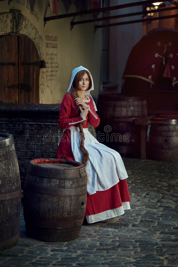 Townswoman in red dress with an apron and chaperone on the street. Costume stylized of later Middle Ages on 15/ 16th century royalty free stock image