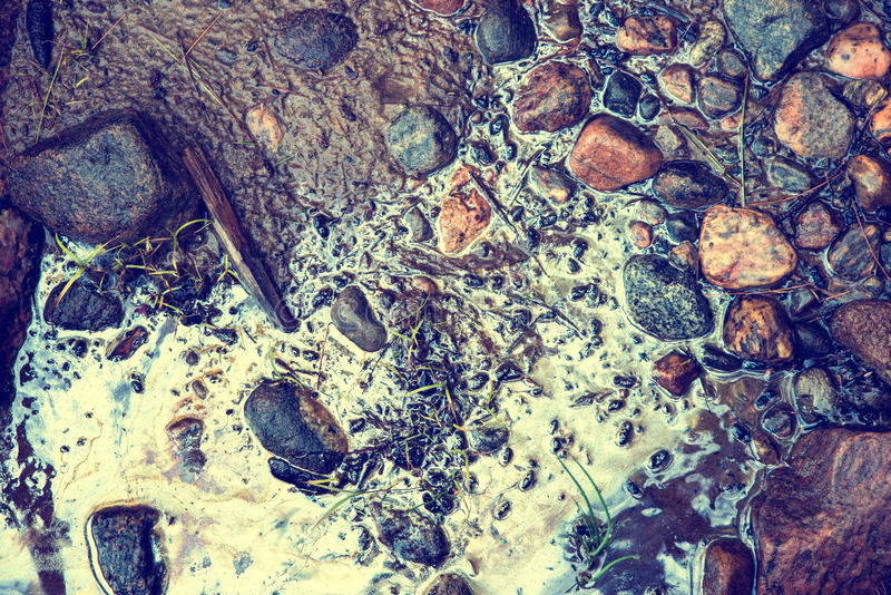 Toxic Beach. Muddy sand and stones at a beach contaminated with toxic chemical gasoline waste. Small patches of grass grow around the stones. Filtered for a royalty free stock images