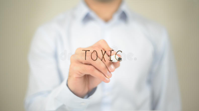 Toxic, Man Writing on Transparent Screen. High quality stock image