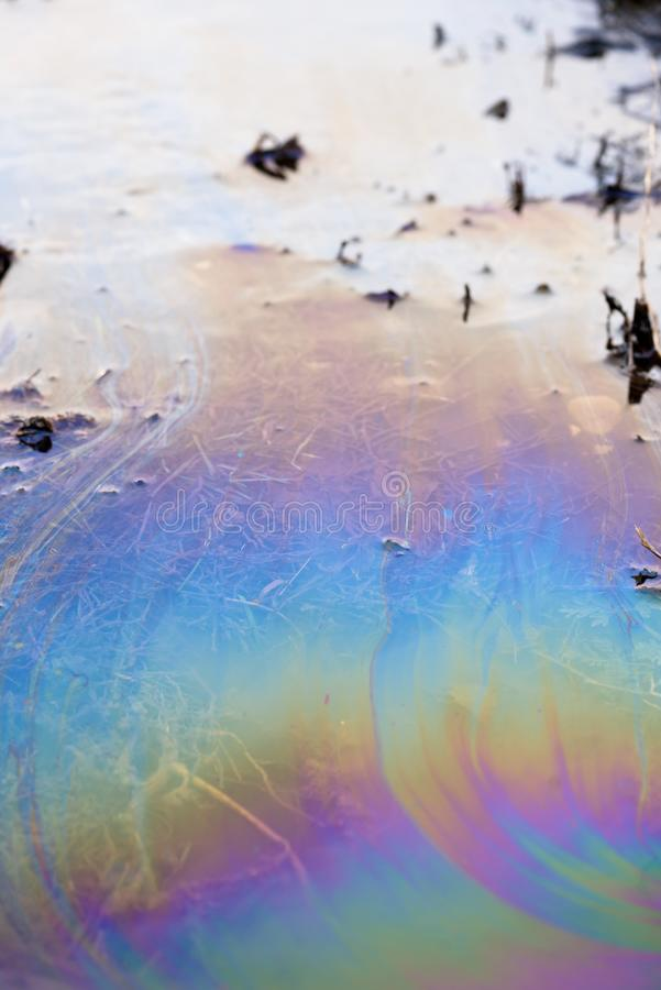 Toxic Oil Chemical Spill on Water Surface. Toxic colours of oil and water in a chemical spill creating a psychedelic blur of rainbow colours. Copyspace area for royalty free stock image