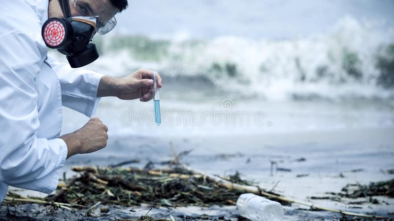 Toxicologist checking polluted water, splashing on shore, environmental disaster. Stock photo royalty free stock photos