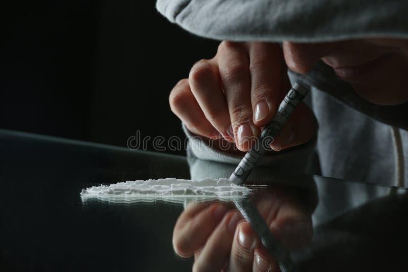 Toxicomane prenant la cocaïne à la table images stock