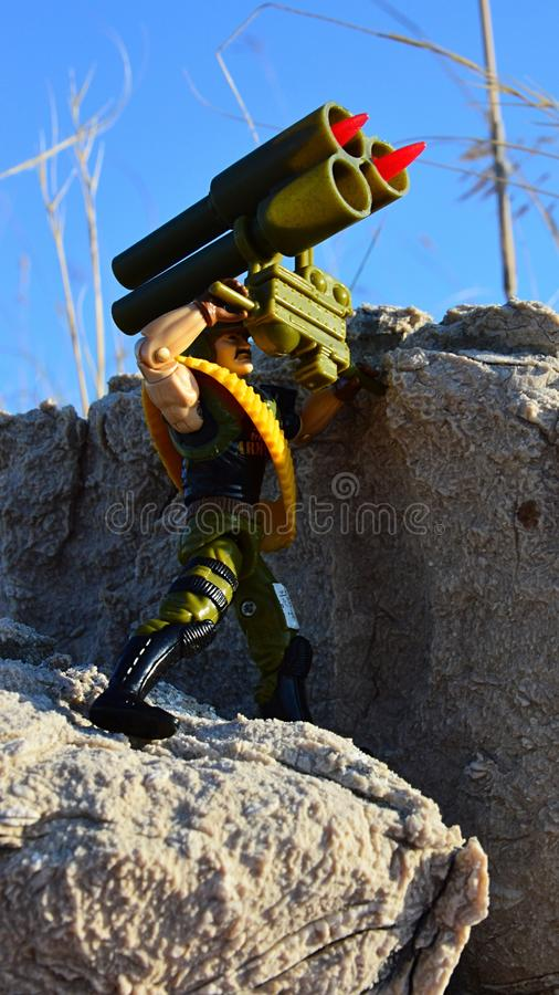 Toy action figure of GI Joe soldier named Backblast standing on coastal rocks with anti aircraft rocket launcher royalty free stock image