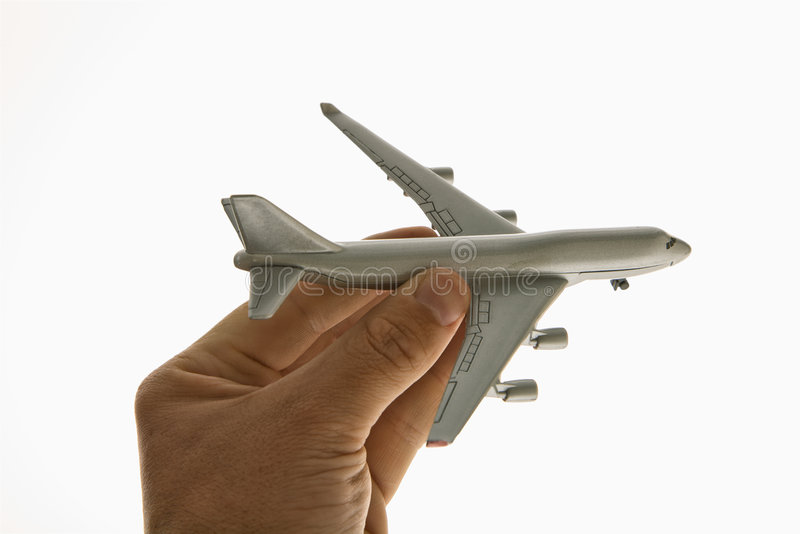 Toy airplane. Hand holding miniature toy airplane royalty free stock images