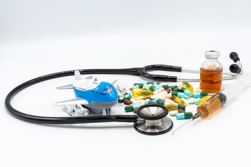 Toy airplane with black stethoscope and assorted drugs imply medical tourism on white black ground stock photography