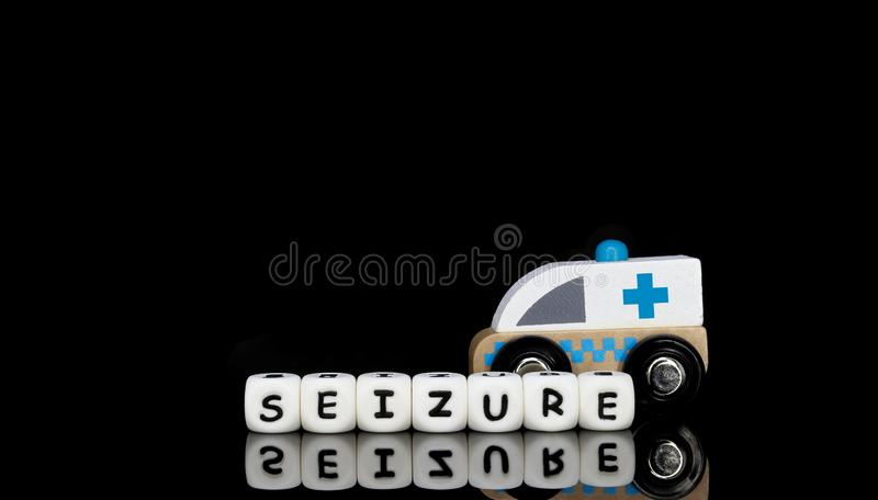 A toy ambulance and a word seizure. Alphabet letters spelling a word seizure with a model ambulance in the background. Medical emergency concept royalty free stock photography