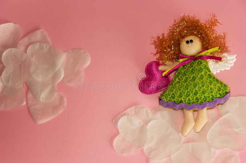 Toy angel on the clouds of white hearts stock images
