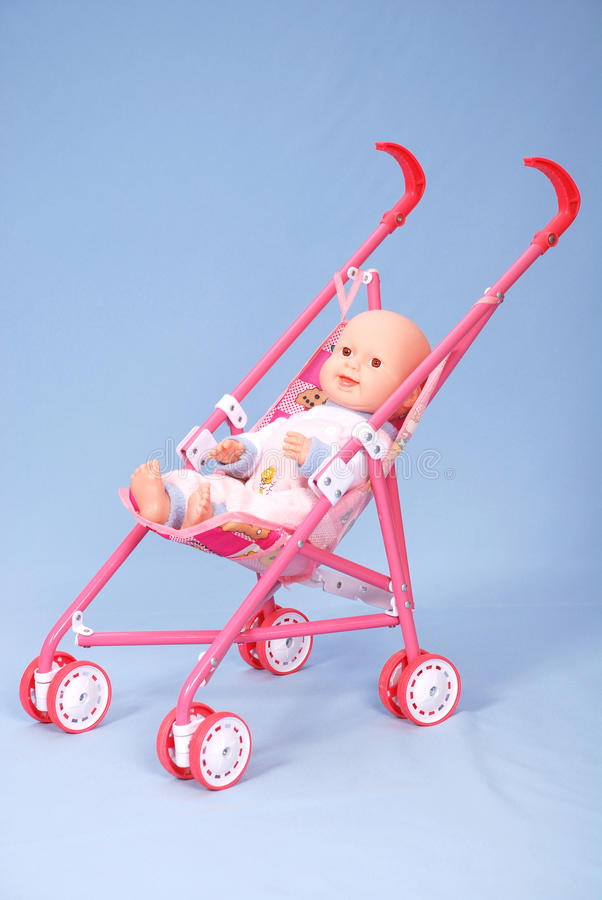 Toy baby buggy on blue background. On a carriage the doll lays royalty free stock image