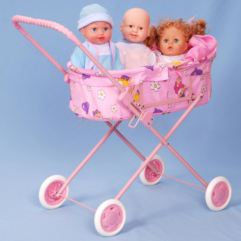 Toy baby buggy on blue background. On a carriage lays three dolls royalty free stock images