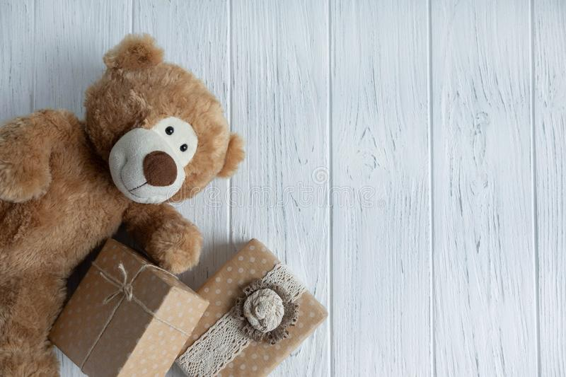 Toy bear, boxes with gifts on a light wooden background. The design of the birthday greeting card. Frame for the text of the. Congratulatory inscription royalty free stock image