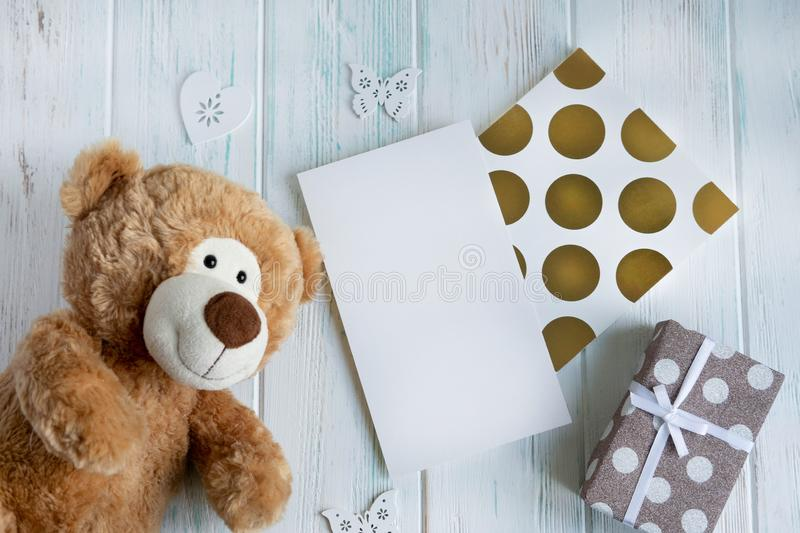 Toy bear, boxes with gifts on a light wooden background. The design of the birthday greeting card. Frame for the text of the. Congratulatory inscription royalty free stock photography