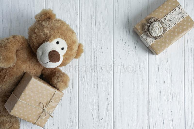 Toy bear, boxes with gifts on a light wooden background. The design of the birthday greeting card. Frame for the text of the. Congratulatory inscription stock photo