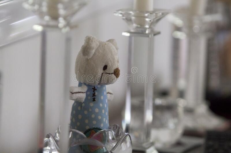 Toy bear in crystal candle holder. Kids` business concept. Close up of a toy bear  put in a crystal candle holder among other decorative glassware. Kids` royalty free stock image