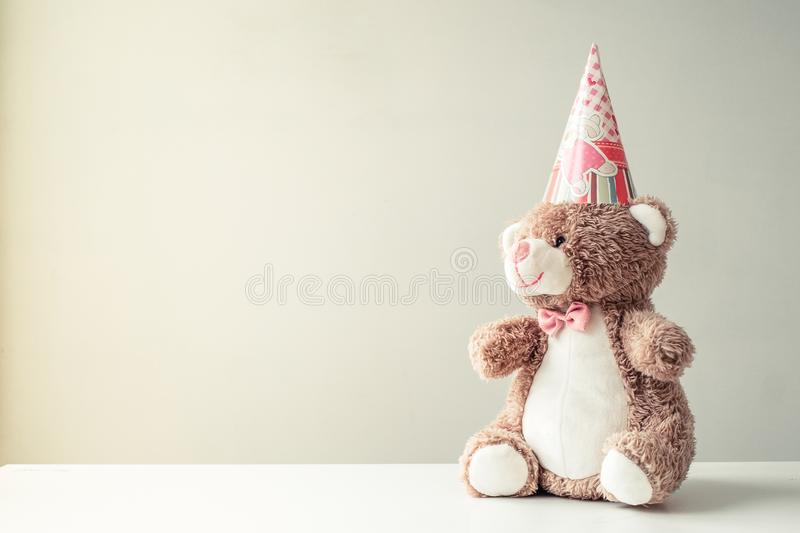 Toy bear handmade in the hood for a birthday. On a gray background stock images