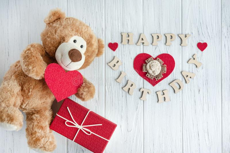 Toy bear with a heart and boxes with gifts on a light wooden background. The design of the birthday greeting card. Frame for the. Toy bear with a heart and boxes stock photography