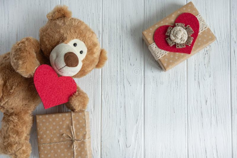 Toy bear with a heart and boxes with gifts on a light wooden background. The design of the birthday greeting card. Frame for the. Text of the congratulatory stock images