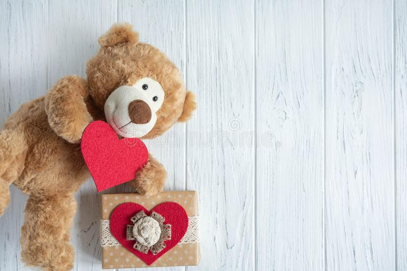 Toy bear with a heart and boxes with gifts on a light wooden background. The design of the birthday greeting card. Frame for the. Text of the congratulatory royalty free stock image