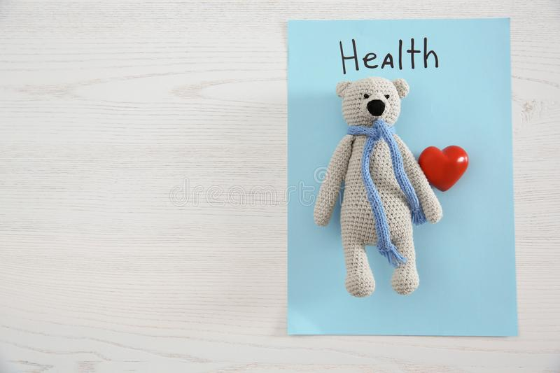 Toy bear, heart, sheet of paper with word HEALTH and space for text on wooden background, top view. Children`s doctor royalty free stock photo