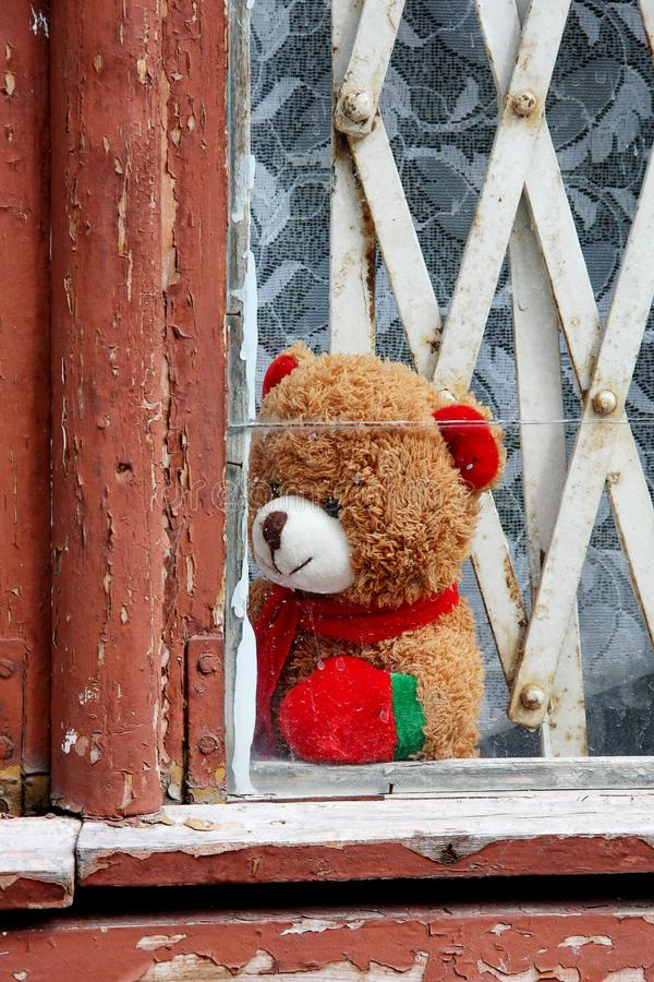 A toy bear sits on the windowsill of an old window with a wooden frame royalty free stock image