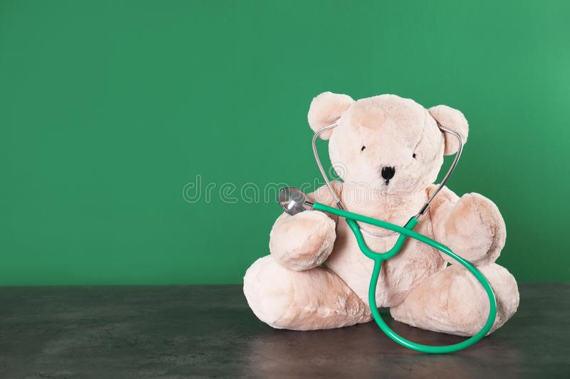 Toy bear with stethoscope on table against color background, space for text. stock photography