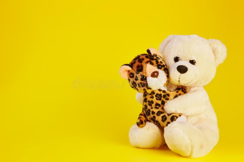 Toy bear and a toy leopard. With a yellow background stock images