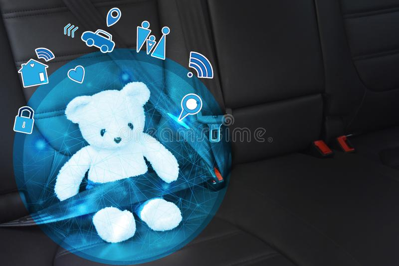 Toy bear white buckled with safety belt in the back seat of car and right empty space for text. Concept and protect children stock photography