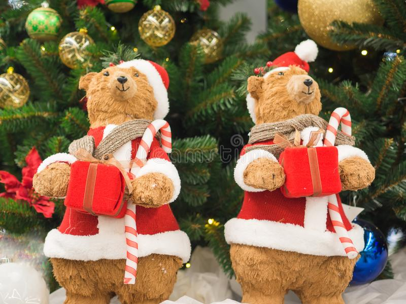 Toy bears dressed as Santa Clauses standing against a Christmas tree holding gift boxes. Christmas and New Year concept royalty free stock image