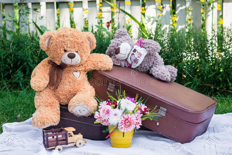 Toy bears sitting on suitcases. Toy bears are sitting on a suitcases in the garden royalty free stock photos