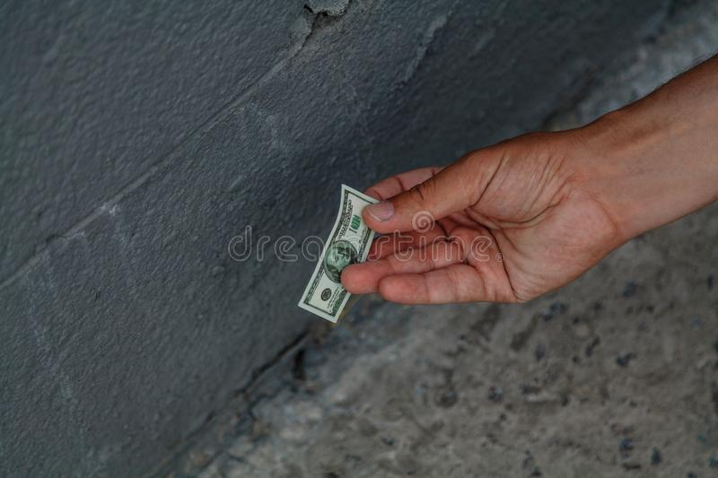 Hand picks up  toy bill from  concrete floor. Toy bill lies on the concrete floor. Man`s hand picks it up royalty free stock photography