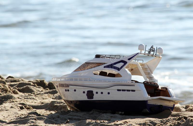 Toy boat on the beach royalty free stock photos