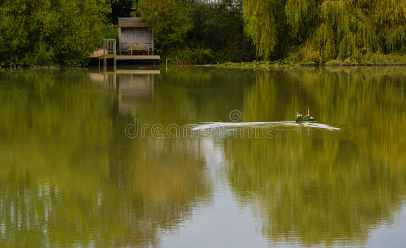 Toy boat on a lake. A toy boat taken on the pond at Wattlehurst Farm stock image