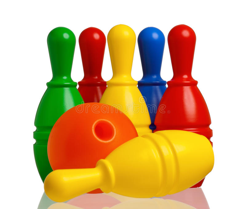 Toy bowling. Colorful plastic skittles of toy bowling with orange ball on a white background stock image