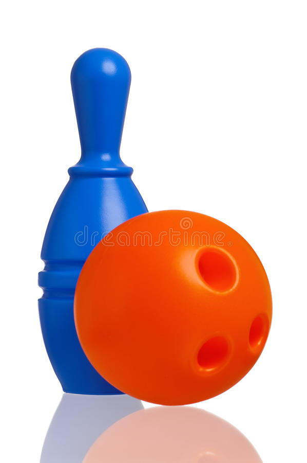 Toy bowling. Single plastic skittle of toy bowling with orange ball isolated on a white background royalty free stock photos